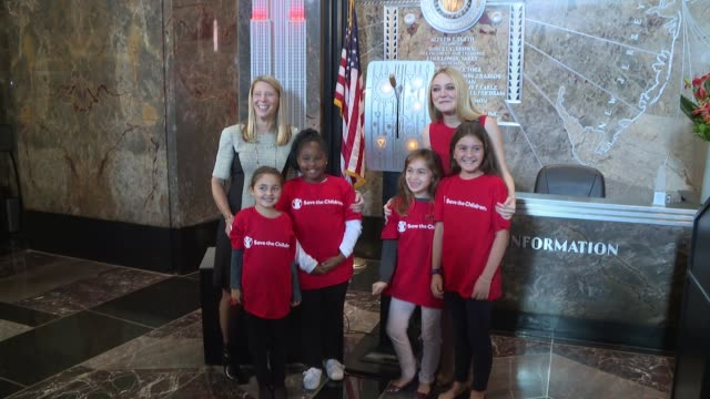 vidéos et rushes de dakota fanning, carolyn miles, save the children's president & ceo and girl supporters flip on the lights at dakota fanning lights the empire state... - directrice