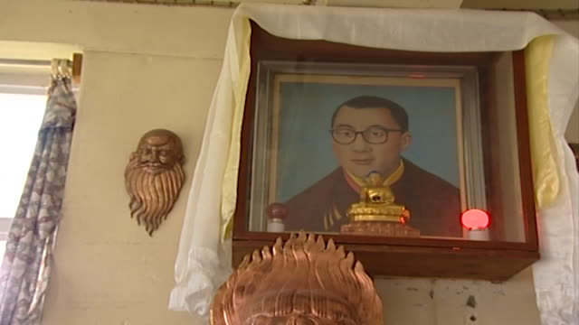dalai lama. low-angle view of a photograph of hh dalai lama as a young man placed in a shrine with a small buddha statue. - traditionally tibetan stock videos & royalty-free footage