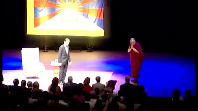 vídeos de stock e filmes b-roll de dalai lama speech at royal albert hall; his holiness, the dalai lama introduced and arriving onto stage as audience applaud sot / dalai lama takes... - cross legged