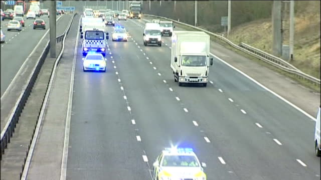 dale cregan trial begins; england: lancashire: ext high angle view of convoy of police cars with flashing lights and prison vans along motorway - crime or recreational drug or prison or legal trial stock-videos und b-roll-filmmaterial