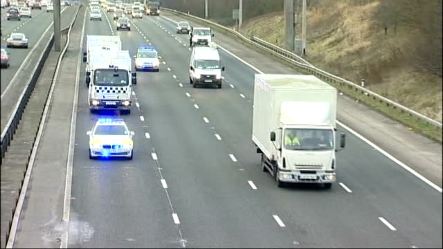 lancashire ext high angle view of convoy of police cars with flashing lights and prison vans along motorway police officer directing cars as prison... - anweisungen geben stock-videos und b-roll-filmmaterial