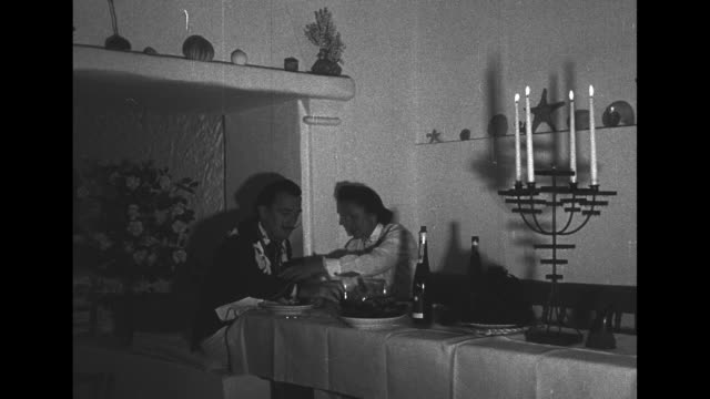 LS Dali and wife at long table with candelabra couple of wine bottles mantle in background with large bouquet of flowers below mantle / MS Dali and...