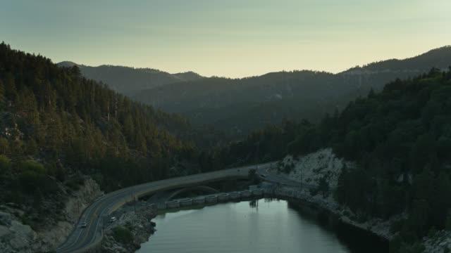 vidéos et rushes de barrage et pont de big bear lake, californie dans l'ombre au coucher du soleil - aérien - barrage