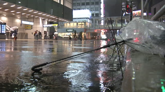 damage from the typhoon was reported around japan a damaged umbrella on the ground in front of jr shinjuku station - typhoon stock videos and b-roll footage