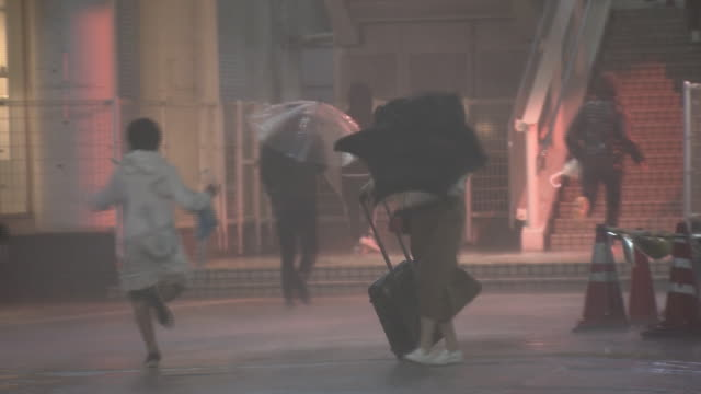 vídeos y material grabado en eventos de stock de damage from the typhoon was reported around japan people are walking on the sidewalk with umbrellas in the storm in front of jr shinjuku station - meteorología extrema