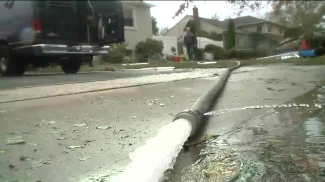 Damage in Nassau County on Long Island 14 Days After Hurricane Sandy Hit A Hose Powered by Generator Drains Water From Home on November 12 2012 in...