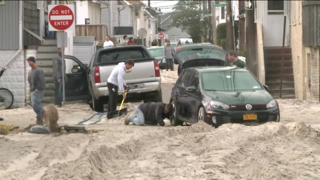 damage in nassau county on long island 14 days after hurricane sandy hit people dig out cars swept up by winds and sand on november 12 2012 in... - nassau stock videos & royalty-free footage