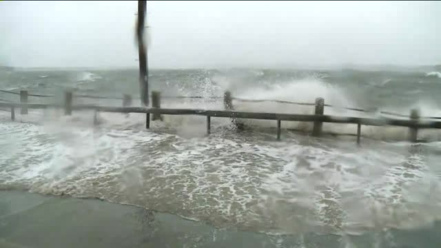 damage in nassau county on long island 14 days after hurricane sandy hit waves crash on road as emergency vehicles drive by on november 12 2012 in... - red cross stock videos & royalty-free footage