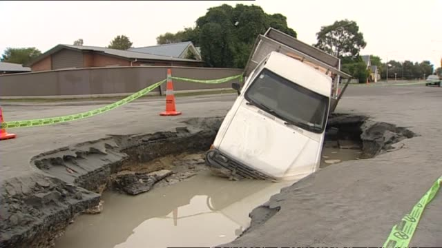 Damage on streets in suburb of Avonside the day following earthquake with small truck sticking out of huge gaping hole in road badly cracked roads...