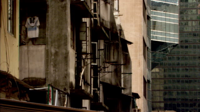 A damaged, abandoned building contrasts with a modern glass high rise nearby. Available in HD.