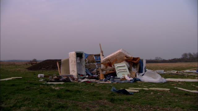 stockvideo's en b-roll-footage met damaged household furnishings are piled in a field in the aftermath of a tornado. - vernieling