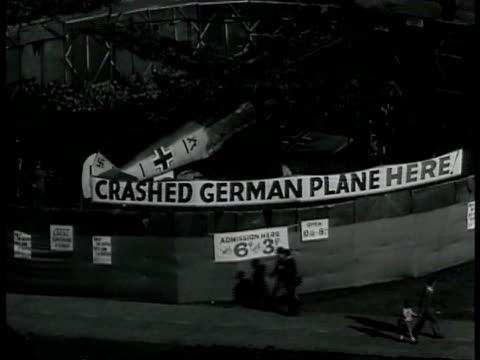 Damaged Messerschmitt German war plane behind fence crowd gathered in front of plane banner 'Crashed German Plane Here' MS Men adjusting damaged...