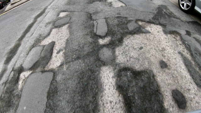 4K: Damaged Road with many Potholes - Driving over, looking down
