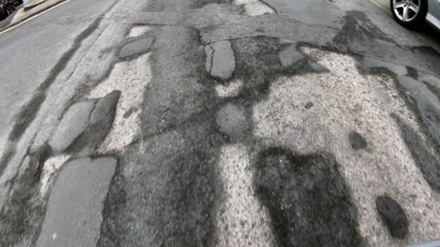 vídeos de stock, filmes e b-roll de 4k: danificada estrada com muitos buracos - dirigindo, olhando para baixo - pista asfaltada