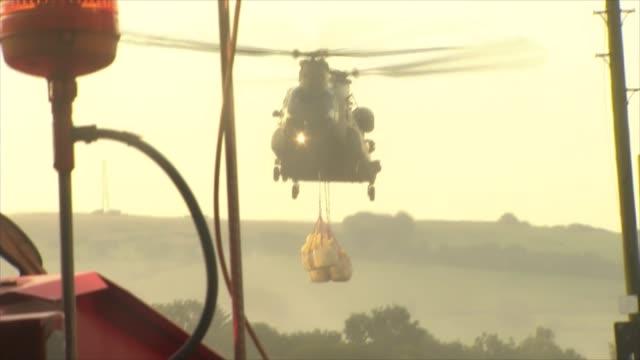 vídeos de stock e filmes b-roll de raf chinook helicopter deployed england derbyshire near whaley bridge toddbrook reservoir ext chinook helicopter lowering sandbags / general views of... - baixar