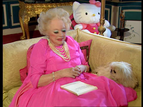 INT Dame Barbara Cartland holding dog looking at framed pictures used as covers for her books LIB EXT Cartland waving LIB INT Dame Barbara Cartland...