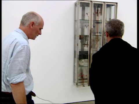 new exhibition; glass and hirst talking about one of the cabinets making up 'apostles' sot cabinet representing st thomas, which has a spear passing... - crucified females stock videos & royalty-free footage