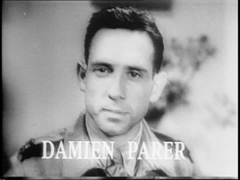 Damien Parer filming in combat / montage of wartime footage shot by Parer close up of Parer 'Tobruk' written in sand scenes of New Guinea Parer's...