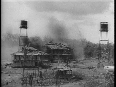 damien parer narrates over footage of marines advancing across an airstrip, soldiers fire rifles / mortar crews fire / mortars explode in a village /... - guam stock videos & royalty-free footage