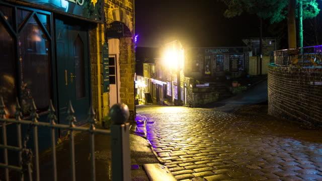 vídeos de stock, filmes e b-roll de damp cobbled village street on winter night - time lapse - aldeia