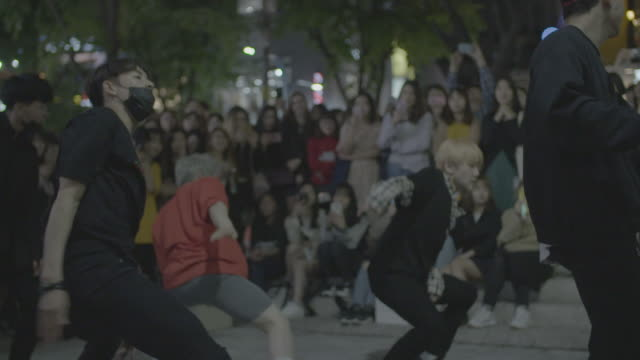 dance group performs on seoul street at night, slow motion - street performer stock videos and b-roll footage