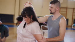 Dance instructor helping women stretch after dance class