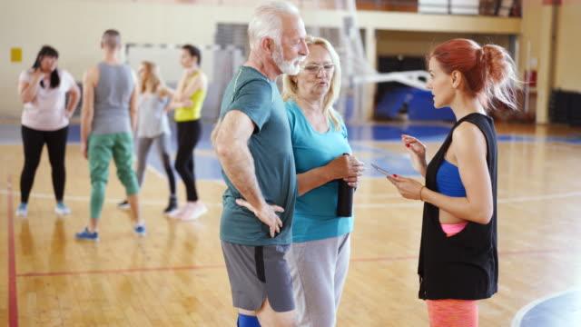 vídeos de stock, filmes e b-roll de instrutor da dança com a tabuleta digital que fala ao par sênior em sua classe - aula de exercícios