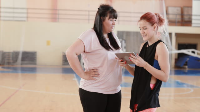dance instructor with digital tablet talking to woman - overweight active stock videos & royalty-free footage