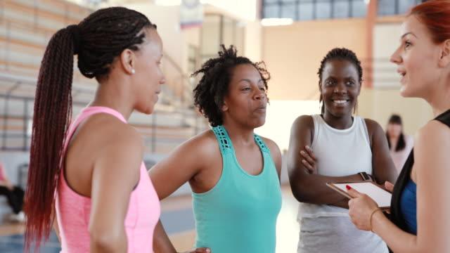 vídeos de stock e filmes b-roll de dance instructor with digital tablet talking to women in her class - adulto de idade mediana