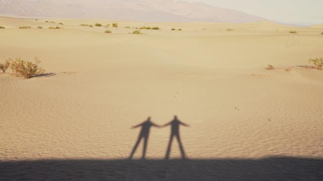 stockvideo's en b-roll-footage met dans van schaduwen. twee vrienden die niet worden gepresenteerd in de video zelf, maar alleen hun schaduwen dansen op de zandduinen in mesquite flats, death valley, californië. - schaduw in het middelpunt