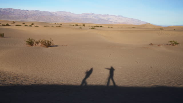 dance of shadows. two friends who are not presented in the video themselves but only their shadows dancing on the sand dunes at mesquite flats, death valley, california. - death valley national park stock videos & royalty-free footage