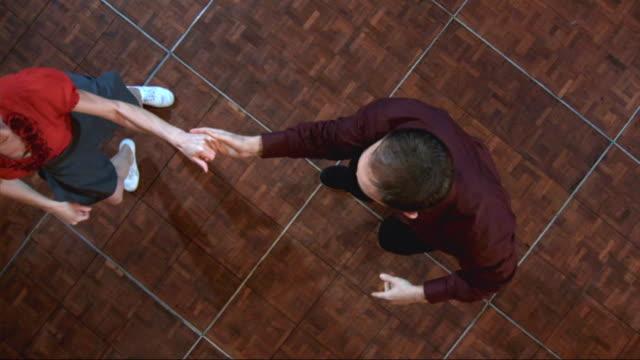 vidéos et rushes de dance partners spin across a dance floor. - dancing