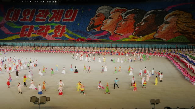 dance perfomance with international costumes during mass games in pyongyang, north korea, dprk. wide shot - spoonfilm stock-videos und b-roll-filmmaterial