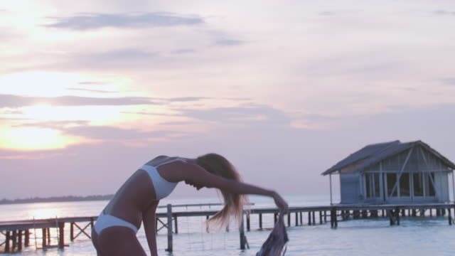 a dance woman dancing with a sarong at sunset. - sarong stock-videos und b-roll-filmmaterial