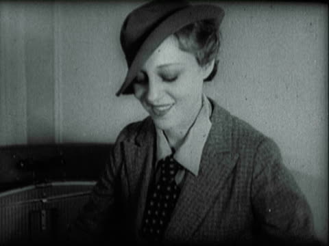 stockvideo's en b-roll-footage met dancer, entertainer, and nightclub nudist sally rand wearing boyish light-colored tweed suit with tie while happily packing feather fan in suitcase,... - 1935