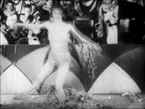 b/w 1928 dancer in skimpy outfit spinning in nightclub floor show / newsreel - 1920 stock-videos und b-roll-filmmaterial