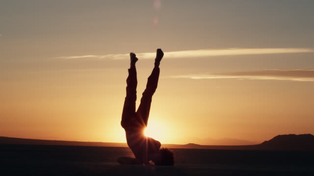 vídeos de stock e filmes b-roll de a dancer performs on the dry lake bed of el mirage, california. - retroiluminado