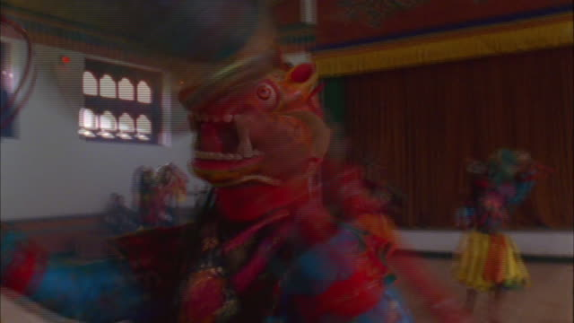 A dancer wearing a dragon mask holds a musical instrument. Available in HD.