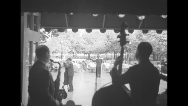 dancers and diners outside at tavern on the green seen from behind musicians a saxophonist and bass player / couple on grass in park man walking... - tavern on the green stock videos & royalty-free footage