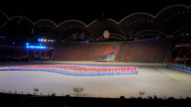 dancers in colors of the national flag performing an amazing wave during mass games in pyongyang, north korea, dprk. wide shot - spoonfilm stock-videos und b-roll-filmmaterial
