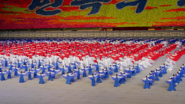 dancers in colors of the national flag performing during mass games in pyongyang, north korea, dprk. medium wide shot - north korea stock videos & royalty-free footage