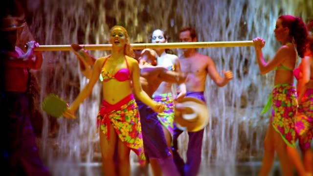 MS dancers in costumes doing limbo on stage with waterfall in background
