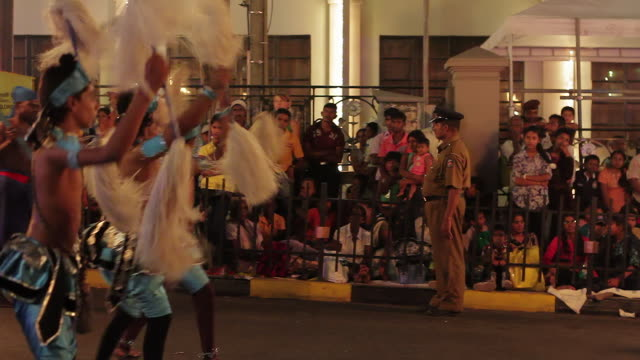 stockvideo's en b-roll-footage met ms tu dancers parade in front of sign 'perahera route' during buddhist festival or procession 'esala perahera' (festival of tooth) audio / kandy, central province, sri lanka - sri lankaanse cultuur