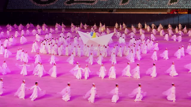 dancers performing a beautiful synchronized ballet formation during mass games in pyongyang, north korea, dprk. wide shot - north korea stock videos & royalty-free footage
