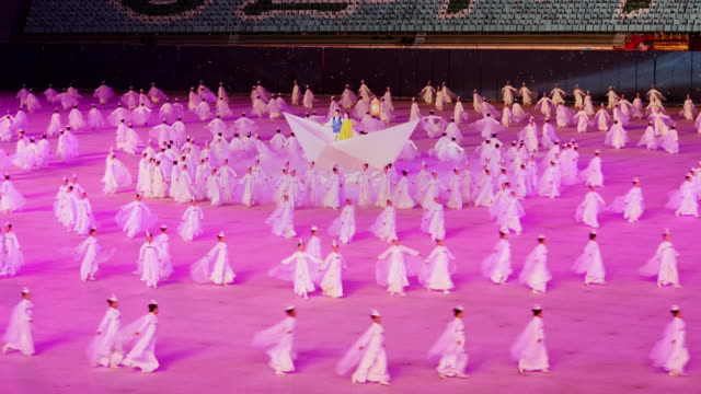 dancers performing a beautiful synchronized ballet formation during mass games in pyongyang, north korea, dprk. medium shot - spoonfilm stock-videos und b-roll-filmmaterial