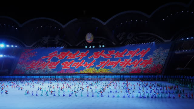 tl dancers performing a beautiful synchronized ballet formation with large shells during mass games in pyongyang north korea dprk wide shot - spoonfilm stock videos and b-roll footage