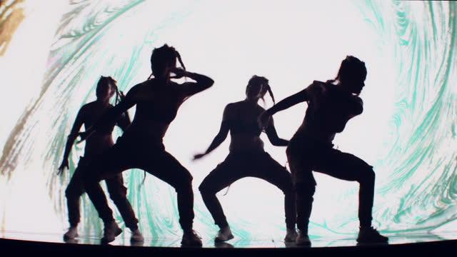tänzer silhouetten auf der bühne mit projektion hintergrund. in surrealer, digitaler landschaft mit neonblitz - tänzerin stock-videos und b-roll-filmmaterial
