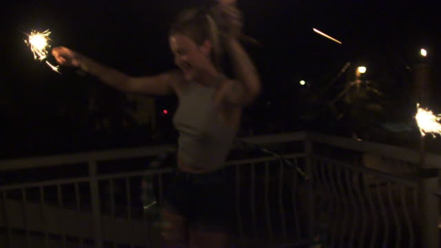 Dancing Caucasian woman with sparklers spinning plastic hoop