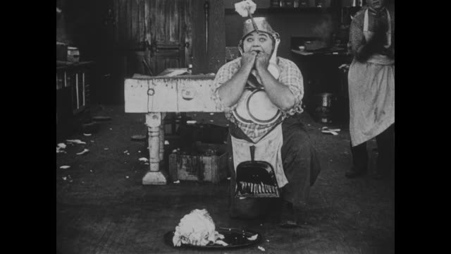 vidéos et rushes de 1918 dancing chef (fatty arbuckle) acts out and dances around the kitchen while adorned with pots and pans - applaudir