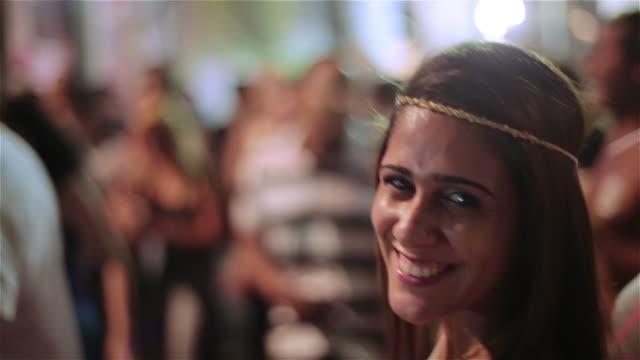 Dancing girl smiles at camera at outdoor concert in Rio de Janeiro